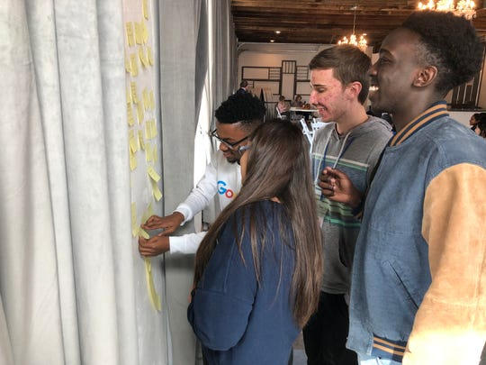 Claude Nduwimana, left, a sophomore at the Academy of Technology, Engineering, Math and Science, places a sticky note on a wall at the SoDA District Courtyard as part of Abilene ISD's SuperCrew meeting Thursday. Nduwimana, joined by Cooper High students Shannon Walker and Jackson Young, center, and Abilene High student Joshua Musonera, right, helped district administrators with a problem.