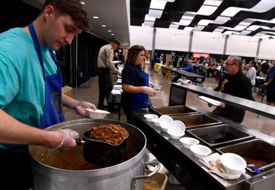 Jimmy Simpson scoops chili from a large pot into a small one to refill pans for Jennifer Eames. The Greater Kiwanis Club of Abilene held its annual Chili Day and Auction on Saturday at the Abilene Convention Center.