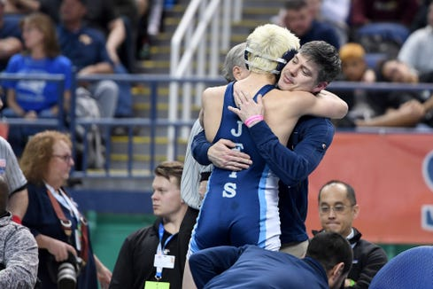 EnkaÕs Corbin Dion is congratulated by coach Mark Harris after he defeated Marvin RidgeÕs Tommy Capul in the 3A 126-pound state title match at the NCHSAA state championship wrestling tournament at the Greensboro Coliseum in Greensboro on Feb. 22, 2020.