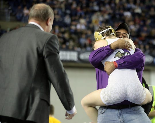 North Kitsap's Holly Beaudoin hugs coach Robert Gomez after winning her first state wrestling title Saturday at Mat Classic.