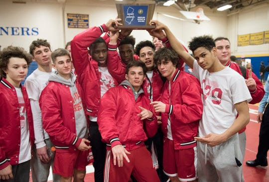 Members of the Paulsboro High School wrestling team celebrate with their trophy after Paulsboro won the District 26 wrestling tournament held at the Rowan College of South Jersey in Deptford, on Saturday, Feb. 22, 2020.