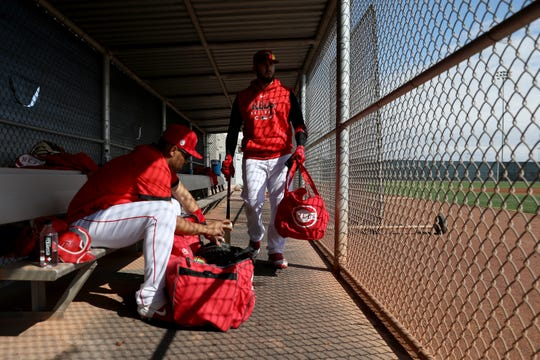 Cincinnati Reds non-roster invitee catcher Francisco Pena (75) left, and second baseman Mike Moustakas (9) gather their equipment from the dugout during spring practice, Sunday, Feb. 23, 2020, at the baseball team's spring training facility in Goodyear, Ariz.