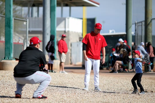 Cincinnati Reds starting pitcher Sonny Gray's (54) son, Gunnar, 5, far right, throws a baseball to Cincinnati Reds minor-league pitching coordinator Kyle Boddy during spring practice, Sunday, Feb. 23, 2020, at the baseball team's spring training facility in Goodyear, Ariz.