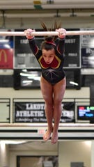 Maycee Herzog of Turpin grips the upper bar at the 2020 Southwest Ohio Gymnastics Championships, Feb. 22, 2020.