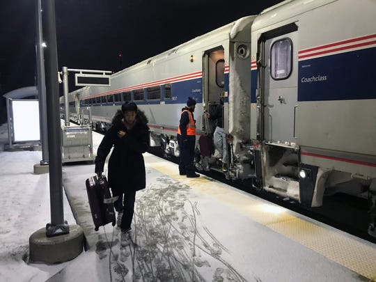 """Amtrak passengers disembark in Troy from the Wolverine service after it arrived more than two hours late on New Year's Eve. The  line, which starts in Chicago, has on-time performance of only 33% -- a problem that Amtrak says is growing worse due to """"freight train interference"""" that makes passenger trains wait while freights pass."""