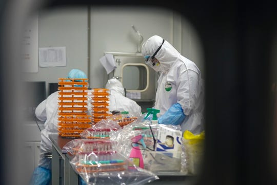 This Saturday, Feb. 22, 2020, photo released by Xinhua News Agency, shows medical workers in protective suits at a coronavirus detection lab in Wuhan in central China's Hubei Province.
