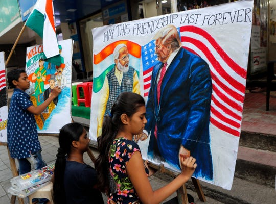 Children from an art school make paintings of U.S. President Donald Trump and India Prime Minister Narendra Modi on Friday ahead of Trump's India visit, in Mumbai, India.
