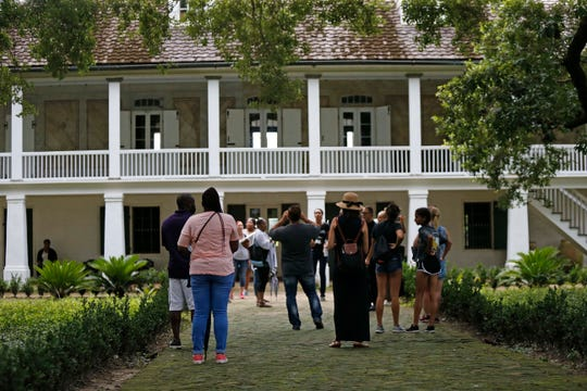 Visitors walk outside the main plantation house at the Whitney Plantation in Edgard, La., on July 14, 2017.