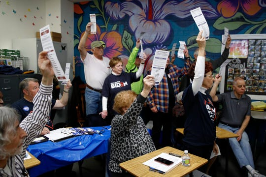 Caucus-goers hold up their ballots, Presidential Preference Cards, at a caucus location at Coronado High School in Henderson, Nev., Saturday, Feb. 22, 2020.