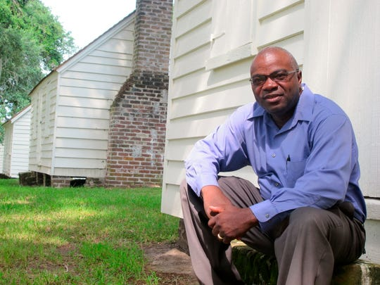 Joe McGill, who works with the National Trust For Historic Preservation, sits outside one of the slave cabins at McLeod Plantation in Charleston, S.C. , on Aug. 14, 2013.
