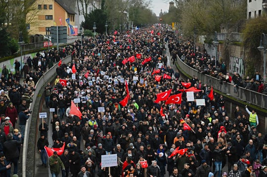 Thousands of people take part in a funeral march in Hanau, Germany, Sunday, Feb. 23, 2020.