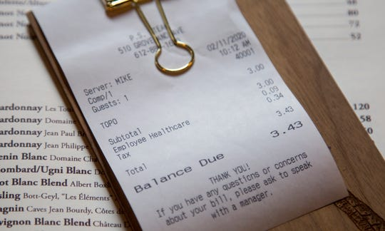 In this Feb. 11, 2020, photo, a line item shows an example of how the charge that Brent Frederick, founder of Jester Concepts, a restaurant group in Minneapolis uses as a 3% voluntary surcharge on guest checks to help pay for health insurance and mental health services and says almost all guests agree to pay it. (AP Photo/Andy Clayton-King)