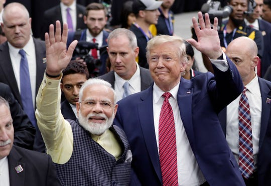 """India Prime Minister Narendra Modi and President Donald Trump walk the perimeter of the arena floor to greet attendants after Modi's speech during the """"Howdi Modi"""" event at NRG Stadium in Houston on Sept. 22, 2019."""