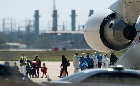 People arrive from Wuhan, China, aboard a chartered Boeing 747 at Joint Base San Antonio-Lackland in Texas Friday, Feb 7, 2020. U.S. officials on Thursday, Feb. 13, announced the country's 15th confirmed case of the new coronavirus — an evacuee from China who had been transported on this flight and was under quarantine in Texas. The patient is now in isolation at a hospital and was reported in stable condition.