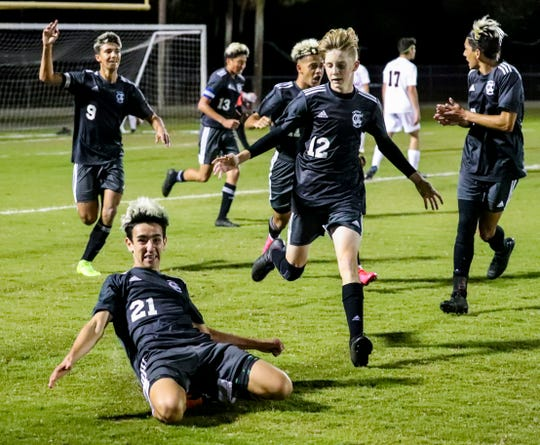 Jason Arias slides to a finish as he celebrates his goal. The Mariner boys soccer team played Bishop Kenny for a spot in the 4A state championship match. The Tritons look to make their first trip to a title match ever in the program's second Final Four.