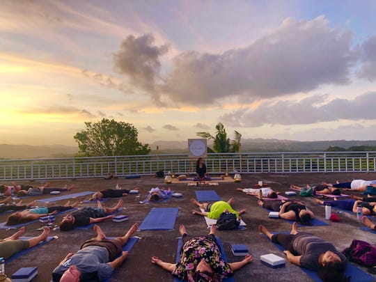 Participants do yoga with teacher Kat Barnett during an Ina Wellness Collective event at Hamamoto Tropical Fruit World on Feb. 15.