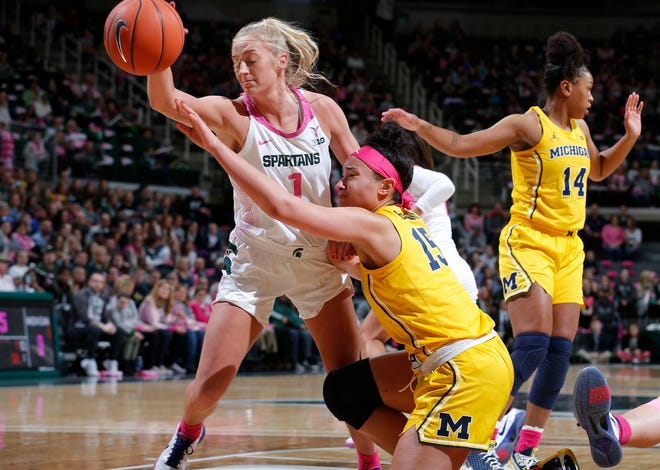Michigan State's Tory Ozment, left, and Michigan's Hailey Brown battle for the ball during the first half of an NCAA college basketball game, Sunday, Feb. 23, 2020, in East Lansing, Mich. (AP Photo/Al Goldis)
