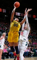 Michigan's Naz Hillmon, left, shoots against Michigan State's Kayla Belles during the first half of an NCAA college basketball game, Sunday, Feb. 23, 2020, in East Lansing, Mich. (AP Photo/Al Goldis)