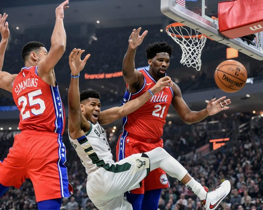 Bucks forward Giannis Antetokounmpo loses the ball while driving for the basket between Ben Simmons (25) and Joel Embiid of the Sixers in the first quarter.