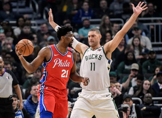 Bucks center Brook Lopez guards  76ers center Joel Embiid on Saturday night at Fiserv Forum.