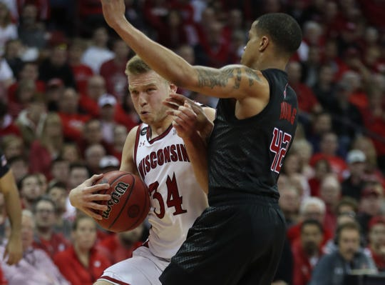 Badgers guard Brad Davison (left) muscles his way to the basket against Rutgers.