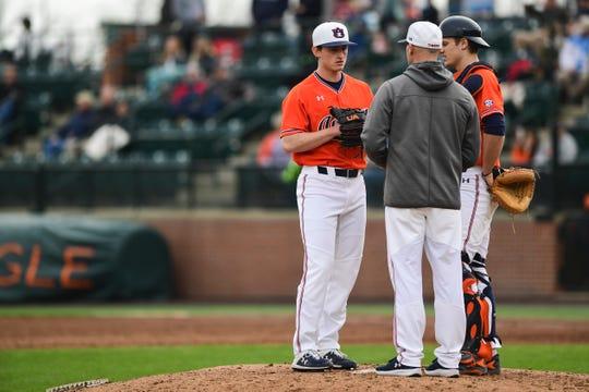 Auburn pitching coach Tim Hudson speaks to pitcher Blake Burkhalter (40) and catcher Matt Scheffler during a game against UCF on Sunday, Feb. 23, 2020.