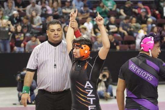 Aztec's Princess Altisi celebrates defeating Miyamura's Nancy Rodriguez for the Girls 160-pound division title in Saturday's New Mexico State Wrestling Championships at the Santa Ana Star Center in Rio Rancho.