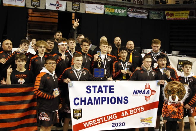 The Aztec wrestling team poses with its 4A state banner in Rio Rancho on Feb. 22, 2020. This is the third consecutive 4A wrestling title in a row for the Tigers.