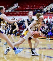 Mercy forward Maya White drives to the basket against Marian.
