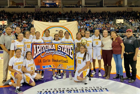 Feb. 22, 2020; Rock Point girls basketball team holds up the AIA 1A girls basketball championship title banner and trophy at Findlay Toyota Center in Prescott Valley, Ariz.