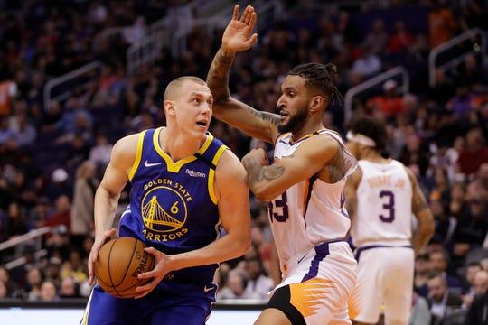 Golden State Warriors forward Alen Smailagic (6) drives as Phoenix Suns forward Jonah Bolden defends during the first half of an NBA basketball game, Wednesday, Feb. 12, 2020, in Phoenix. (AP Photo/Matt York)