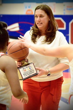 Port Huron coach Becky Gilbert holds the championship trophy after beating Grosse Pointe North in the Macomb Area Conference Red/White girls basketball title game on Saturday, Feb. 23, 2020, at Warren Cousino.