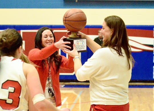 Port Huron athletic director Jillian Ciesielski presents coach Becky Gilbert with the championship trophy after the Big Reds beat Grosse Pointe North in the Macomb Area Conference Red/White girls basketball title game on Saturday, Feb. 23, 2020, at Warren Cousino.