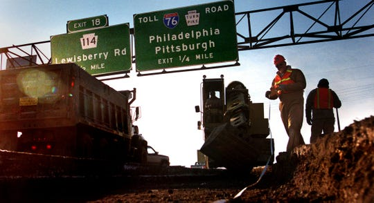 A Penn Dot inspector measures an excavation that will be paved as a temporary roadway near the Pennsylvania Turnpike interchange in 1993.