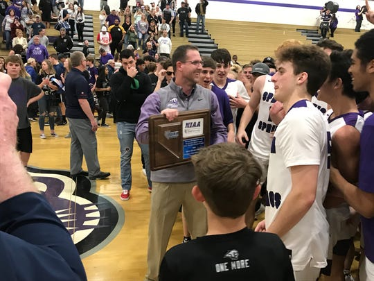 Spanish Springs beat Reed, 50-49, on Saturday for the Northern 4A Regional boys basketball title. Coach Kyle Penney holds the trophy.