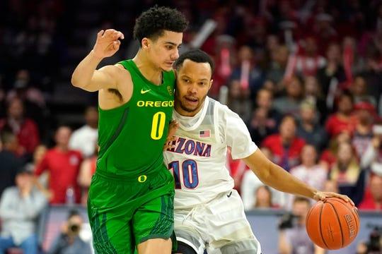 Arizona guard Josh Green (0) drives on Oregon guard Will Richardson (0) in the second half of an NCAA college basketball game Saturday, Feb. 22, 2020, in Tucson, Ariz. Oregon won 73-72 in overtime.