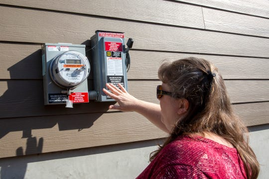 Jennifer Morace shows the meter that tracks the solar power generated at her home in West Salem on Feb. 21, 2020.