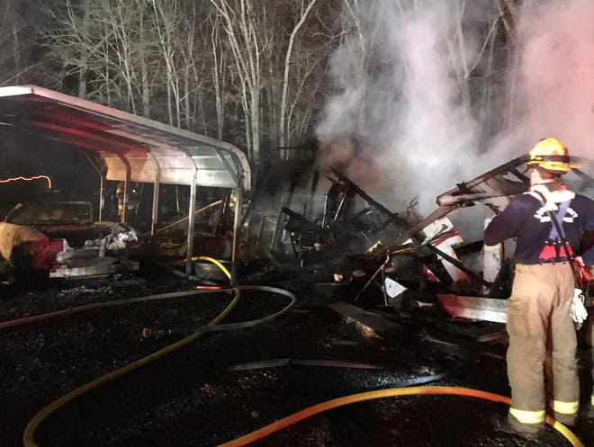 A fire on Sunset Hill Lane destroyed an outbuilding and a carport Saturday night, consuming two vehicles in the process.