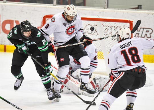 St. Cloud State's Luke Jaycox watches as the puck jumps high next to  North Dakota's Cole Smith in front of the SCSU goal during the first period of the Saturday, Feb. 22, 2020, game at the Herb Brooks National Hockey Center in St. Cloud.