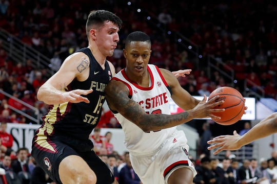 North Carolina State's C.J. Bryce, right, drives the ball around Florida State's Dominik Olejniczak (15) during the first half of an NCAA college basketball game in Raleigh, N.C., Saturday, Feb. 22, 2020. (AP Photo/Karl B DeBlaker)