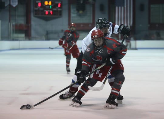 North Rockland's Christian O'Malley (8) works the puck toward the net during the Red Raiders' 4-3 win over Rye Town/Harrison in a first round Div. 1 ice hockey playoff game at Playland Park in Rye on Saturday, February 22, 2020.
