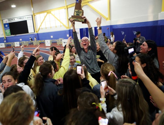 Padua's Anastasia Watson holds the team trophy high after the Pandas took the girls team title in the DIAA Indoor Track and Field Championships on Feb. 22. Columnist Brad Myers believes if a spring sports season can be held, the focus should be on still conducting DIAA championships.