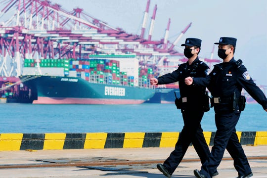In this Feb. 19, 2020, photo, police officers wearing face masks patrol at a container port in Qingdao in eastern China's Shandong Province. China on Friday, Feb. 21 suspended more punitive tariffs on imports of U.S. industrial goods in response to a truce in its trade war with Washington that threatened global economic growth.
