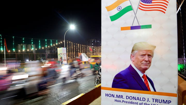 Motorists ride on a decorated bridge U.S. President Donald Trump is expected to take during his visit in Ahmedabad, India, Sunday, Feb. 23, 2020.