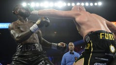 Deontay Wilder and Tyson Fury box during their WBC heavyweight title bout.
