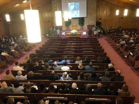 Attendees at Merkel Church of Christ watch a tribute video to pilot Chase Hunter Bellah, 31. Bellah was remembered as a traveler who had quite a shoe collection.
