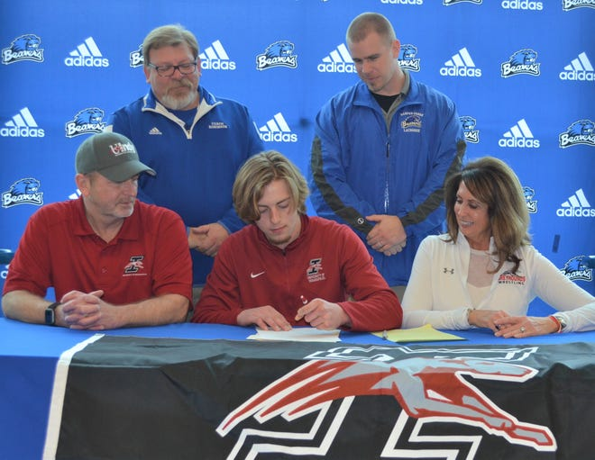 Harper Creek senior Ryan Vette, center, is joined by his family and coaches as he signs a National Letter of Intent to play lacrosse at the University of Indianapolis Monday at Harper Creek  High School.