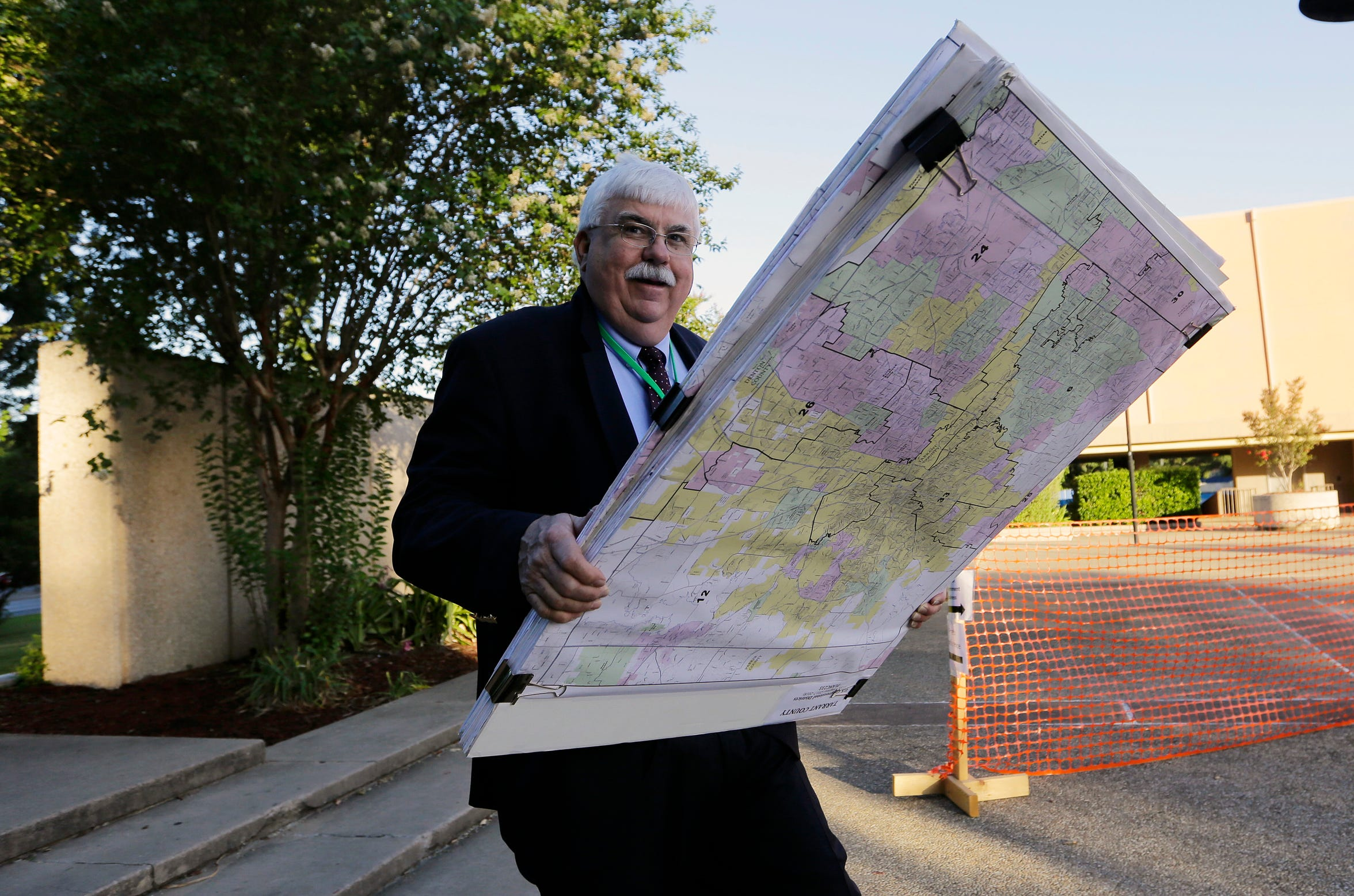 Russ Tidwell, a former lobbyist who is helping minority rights groups sue Texas over Republican-drawn voting maps, holds a set of maps as he makes his way to the federal courthouse, Monday, July 10, 2017, in San Antonio, where a redistricting trial was held.