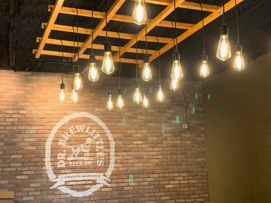 Edison lighting illuminates the Dr. Brewlittle's Beer Co. logo on a brick wall in the Maple Shade tasting room.