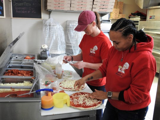 Kellie Corbin and Janell Williams make pizza at Dany's Pizzeria inside M2 Drive Thru. They offer pizzas, subs, stromboli, side salads and dessert pizzas. It opened Feb. 15.